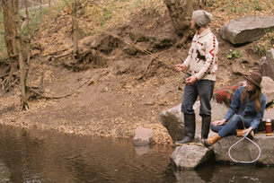 Young couple in a forest, fishing in a river.の写真素材 [FYI02857796]