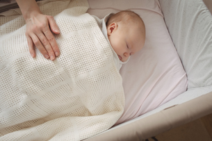 Mother hand on sleeping baby at homeの写真素材 [FYI02857808]