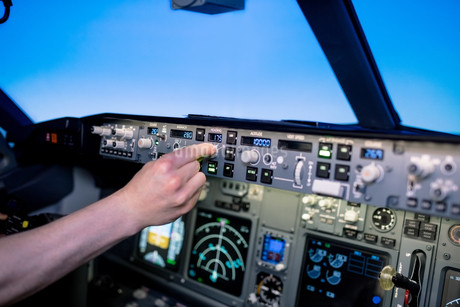Cropped hand of young male pilot switching control in cockpitの写真素材 [FYI02857812]