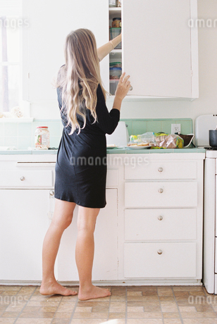 A woman with long blond hair standing barefoot in a kitchen, opening a cupboard.の写真素材 [FYI02857815]