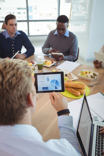 High angle view of businessman using digital tablet at breakfast tableの写真素材 [FYI02857818]