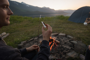 Man cooking sausage on campfireの写真素材 [FYI02857836]