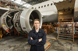 Male aircraft maintenance engineer standing with arms crossed at airlines maintenance facilityの写真素材 [FYI02857838]