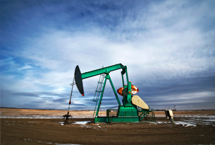An oil pump jack at a drilling site for oil, an oil field in Saskatchewan.の写真素材 [FYI02857842]