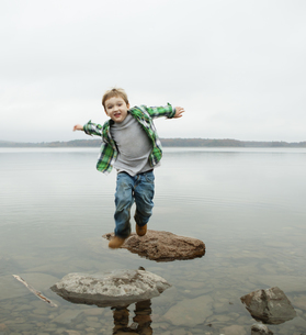 A boy jumping across stepping stones at a lake.の写真素材 [FYI02857845]