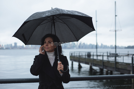 Woman talking on phone while holding umbrella by riverの写真素材 [FYI02857850]
