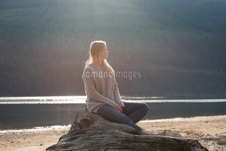 Young woman sitting on log at lakeshoreの写真素材 [FYI02857852]