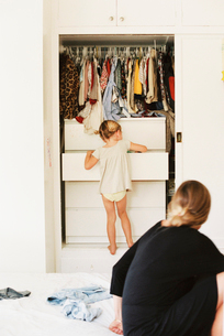 Young girl looking for clothes in a chest of drawers, her mother sitting on a bed, watching.の写真素材 [FYI02857884]