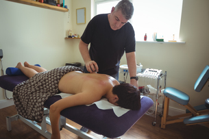 Therapist giving cupping therapy to manの写真素材 [FYI02857885]