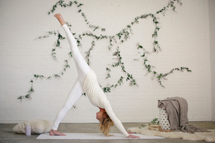 A blonde woman in a white leotard and leggings on an exercise mat, bending down, her leg raised.の写真素材 [FYI02857886]