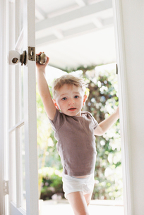 Young boy wearing T-Shirt and pants opening a door.の写真素材 [FYI02857896]