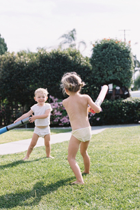 Young girl and young boy, two children wearing T-Shirt and shorts playing in a garden.の写真素材 [FYI02857901]