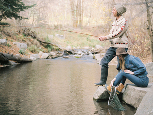 Young couple in a forest, fishing in a river.の写真素材 [FYI02857903]
