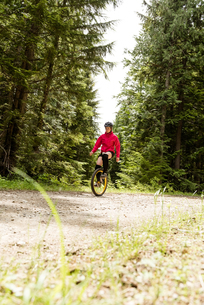 Surface level view of woman riding unicycle on dirt roadの写真素材 [FYI02857907]