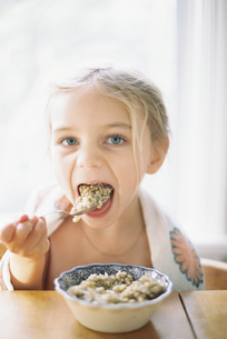 Young girl sitting at a table, eating breakfast from a bowl.の写真素材 [FYI02857915]
