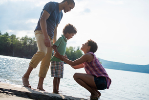 A family, parents and son spending time together by a lake in summer.の写真素材 [FYI02857916]