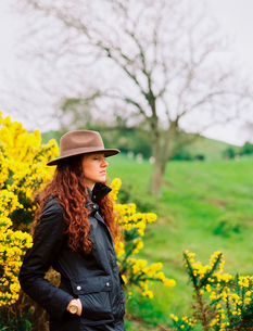 A woman with long curly hair wearing a hat, by a flowering gorse bush.の写真素材 [FYI02857919]