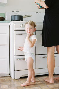 A woman and a child, a young boy standing barefoot in a kitchen.の写真素材 [FYI02857920]