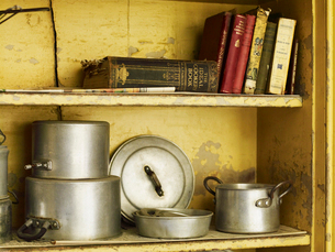 Old well worn recipe books and pots and pans on a kitchen shelf.の写真素材 [FYI02857925]