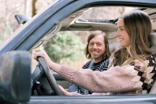 Smiling young couple driving in their car.の写真素材 [FYI02857936]
