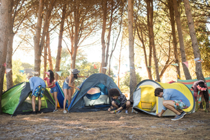 Young friends setting up their tents on fieldの写真素材 [FYI02857938]