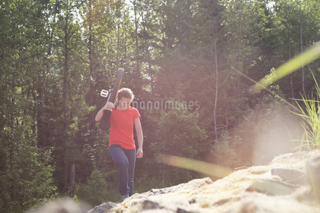 Young female hiker carrying unicycle on rocksの写真素材 [FYI02857955]
