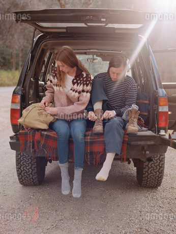 Young couple sitting in the back of their car, putting on boots.の写真素材 [FYI02857963]