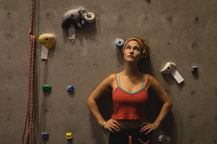 Female athlete with hands on hip looking up while standing by climbing wallの写真素材 [FYI02857969]