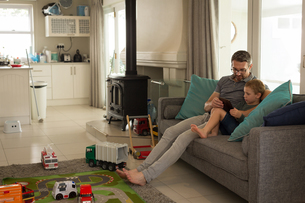 Father and son using digital tablet in living roomの写真素材 [FYI02857976]