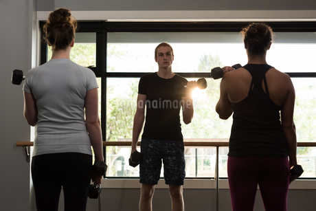 Trainer assisting women in exercising with dumbbellsの写真素材 [FYI02857978]