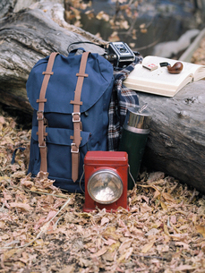 Hiking equipment, a backpack, torch, flask and camera by a tree trunk. A pipe lying on an open book.の写真素材 [FYI02857982]