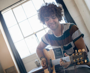 Loft living. A young man playing guitar.の写真素材 [FYI02857986]