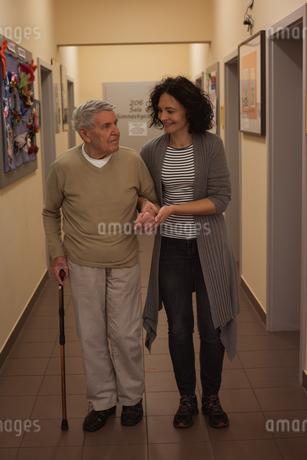 Caretaker assisting senior man while walking in corridorの写真素材 [FYI02857989]