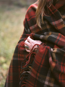 Young blond woman wearing a hat, wrapped in a blanket.の写真素材 [FYI02857991]