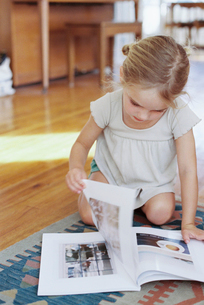 Young girl sitting on the floor, reading a lifestyle magazine.の写真素材 [FYI02858009]