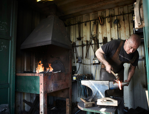 Blacksmith shaping a hot piece of iron on an anvil in a traditional forge with an open fire.の写真素材 [FYI02858011]