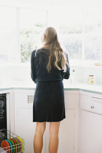 Rear view of a woman with long blond hair standing at a kitchen sink.の写真素材 [FYI02858018]