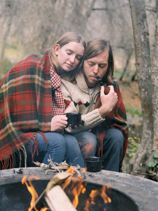 Young couple sitting by a fire pit, wrapped in a blanket.の写真素材 [FYI02858023]