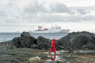 Man walking along rocks by the sea, a polar research vessel in the background on the ocean.の写真素材 [FYI02858026]