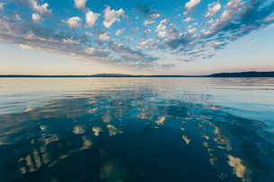 Dramatic clouds and sky reflecting over calm ocean water at dusk, Hood Canal water channel near Pugeの写真素材 [FYI02858028]