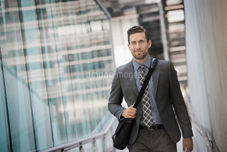 A man carrying a computer bag with a strap on a city walkway.の写真素材 [FYI02858036]