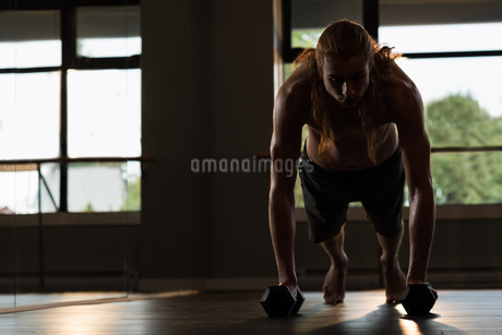 Man doing push-ups with dumbbellsの写真素材 [FYI02858049]