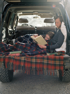 Young couple lying in the back of their car, reading a book.の写真素材 [FYI02858053]