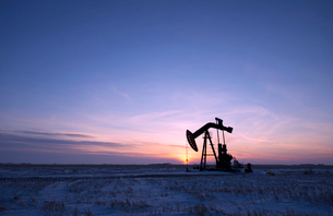 An oil drilling rig and pumpjack on a flat plain in the Canadian oil fields at sunset.の写真素材 [FYI02858059]