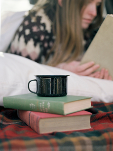 Young woman reading a book, a mug standing on two books.の写真素材 [FYI02858070]