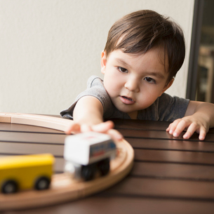 Young boy playing with a wooden train set.の写真素材 [FYI02858072]