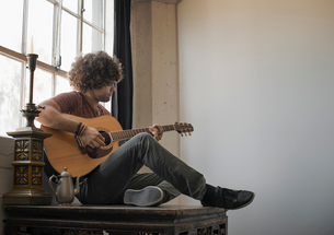 Loft living. A young man playing guitar sitting by a window.の写真素材 [FYI02858083]