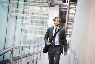 A man carrying a computer bag with a strap on a city walkway.の写真素材 [FYI02858084]