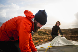 Two men holding and putting up a small tent in open space. Wild camping.の写真素材 [FYI02858099]