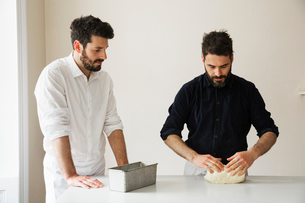 Two bakers standing at a table, kneading bread dough, a metal baking tin.の写真素材 [FYI02858107]